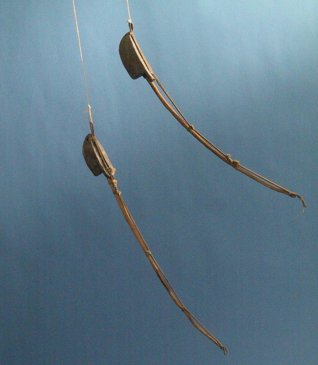 Fiskesøkke til dorgefiske. Støpt blylodd, spikket einerpinne festet i hull i loddet, forsterket m. dobbelt snøre, bundet til loddet og til pinnen. Båtformet blylodd, buet pinne