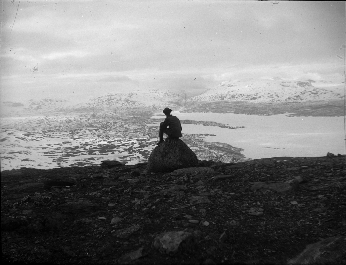 Man i uniform sitter på en sten och ser ut över fjällvy, Sverige