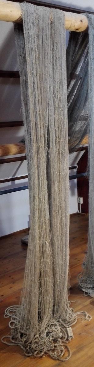 """Lyst torskegarn i bomull, frå ca 1910. Maskestørrelse 14,5 cm (frå hjørne til hjørne). Manglar flyte- og synkeelement. Merka med to firkanta treklossar innsvidd """"O. STENSUND SULEN"""""""