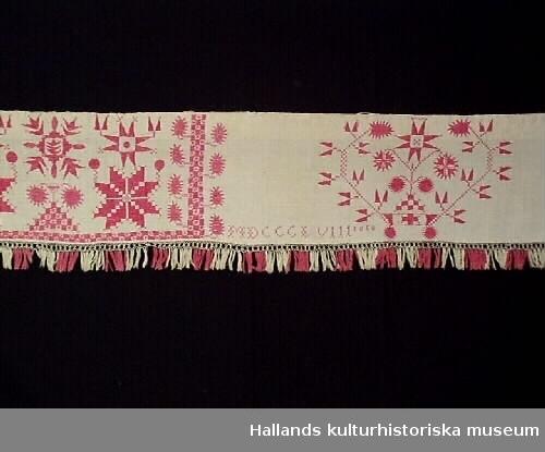 """Hängkläde av linnelärft. Med hallandssöm i nio mönsterpartier av ljusrött bomullsgarn. Vid fållen nertill en smal knytning i linne, vid vilken en ljusröd och vit frans är knuten. I övre kanten en tretrådig linnesnodd, fäst med kaststygn. Monogram med korsstygn: """"MDCCCL VIII 1858."""" Längd (620) 627 - 130 cm. Bredd (utan frans) 33 cm. Frans 7 cm. Frans +:70 mm. Teknik: Vävt, lärft, Sytt, kastsöm, Broderat, hallandssöm, korsstygn, Knutet. Bild 2: Föremålet i utställningen """"Halland genom tiderna""""."""