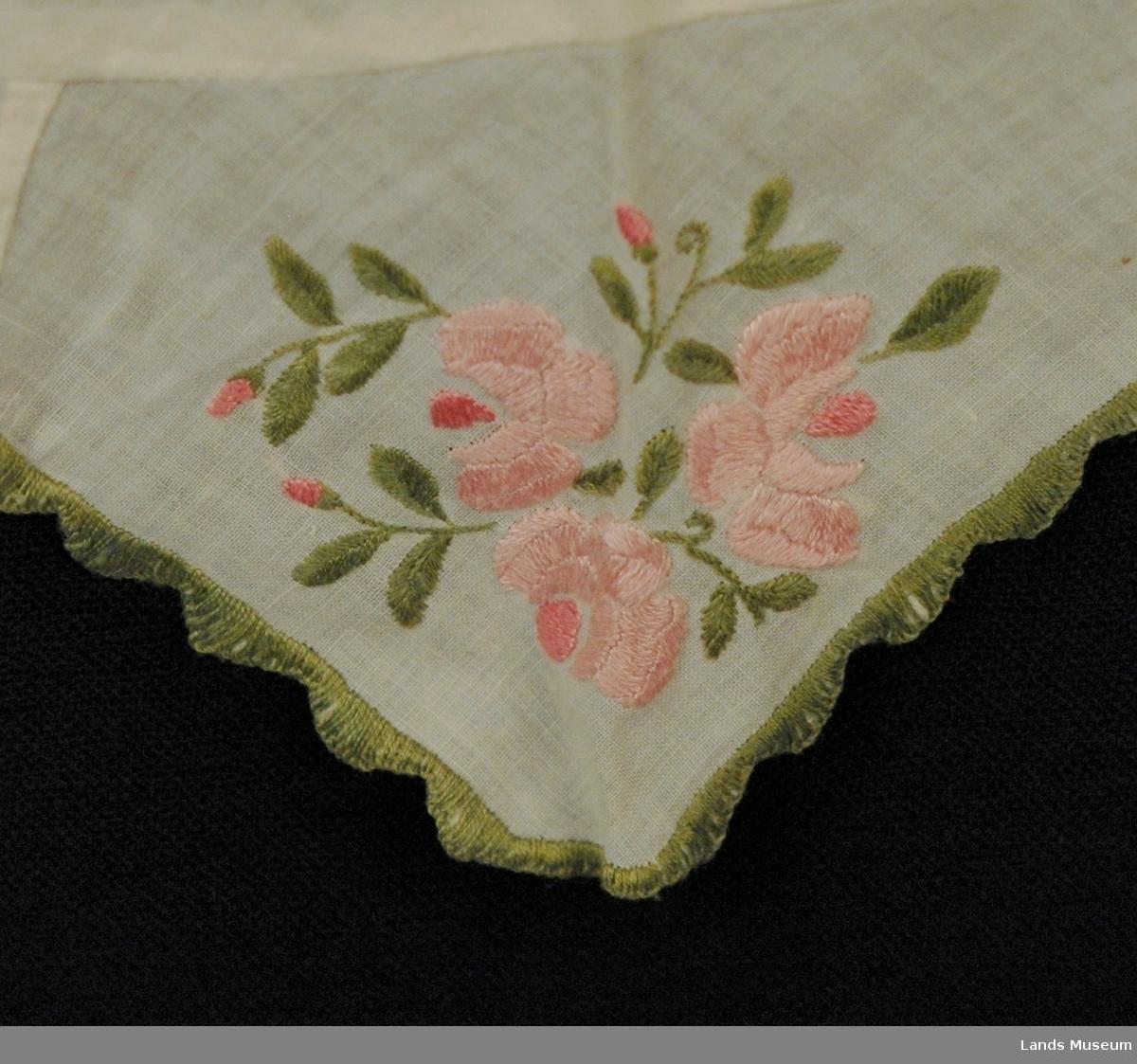 """Halvparten av ein krage. Tynt bomullstoff i tre """"spisser"""". Blomstermotiv på alle spissene, rosa blomster og grøne stilker og blad. Grøn tungekant som avslutning."""