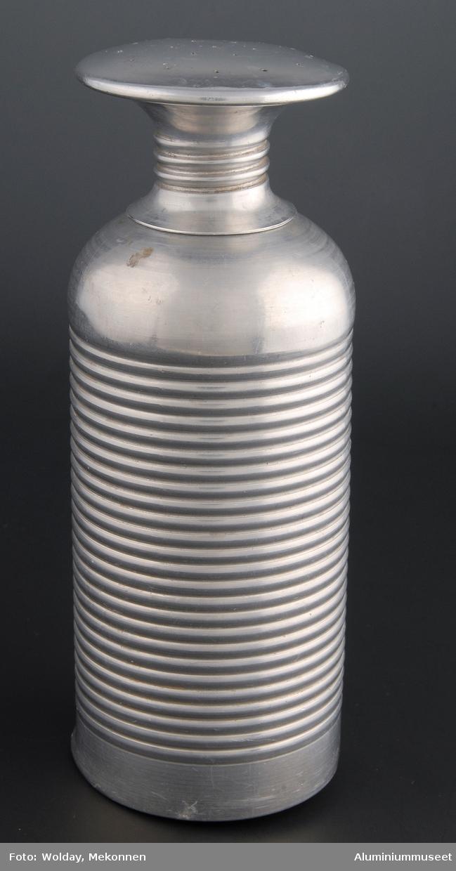 Teknikk: Dynkeflasken er presset i tre trekk i mellomstore presser. Se bilde nr. 19 til høyre. Flasken er videre håndtrykket  til ca. 50 mm. halsåpning og rillet på deledor .Resten av halsåpning og tut er trykket og renskåret på frihånd mot en gjenget dor. Kork med sil er presset i mellomstor presse. Silhullene er lokket i eksenterpresse. Stussen med gjenger er håndtrykket på frihånd mot en gjenget dor. Form: Flaskefasong med stor siltut