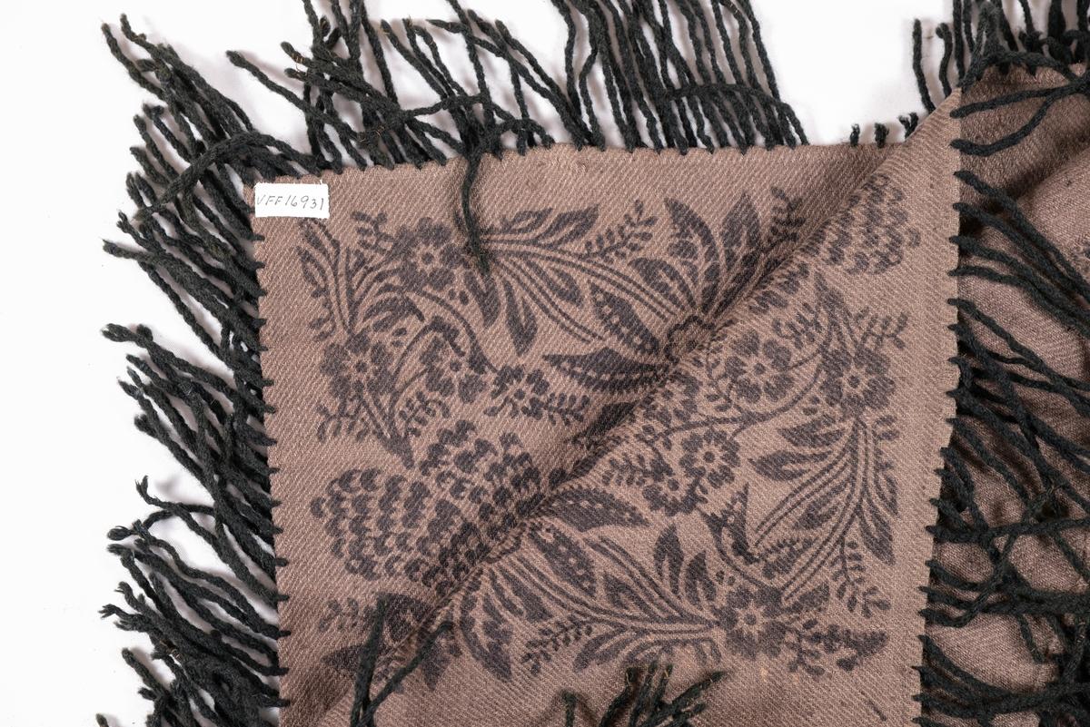 Sjal i kypertvove lys brunt ulltøy. Sett saman av to stykker med saum på midten. Påtrykt svart mønste med blomstermotiv. Falda rundt for hand. Svarte påsydde, tvinna frynser av ullgarn. Eitt stort hol , og mange små.