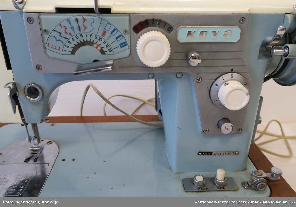 Symaskin med koffert. Maskinen er elektrisk med pedal, åpen remdrift og diverse syprogrammer.