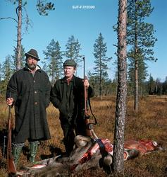 To stolte elgjegere poserer ved en nyskutt elg på ei myr i S