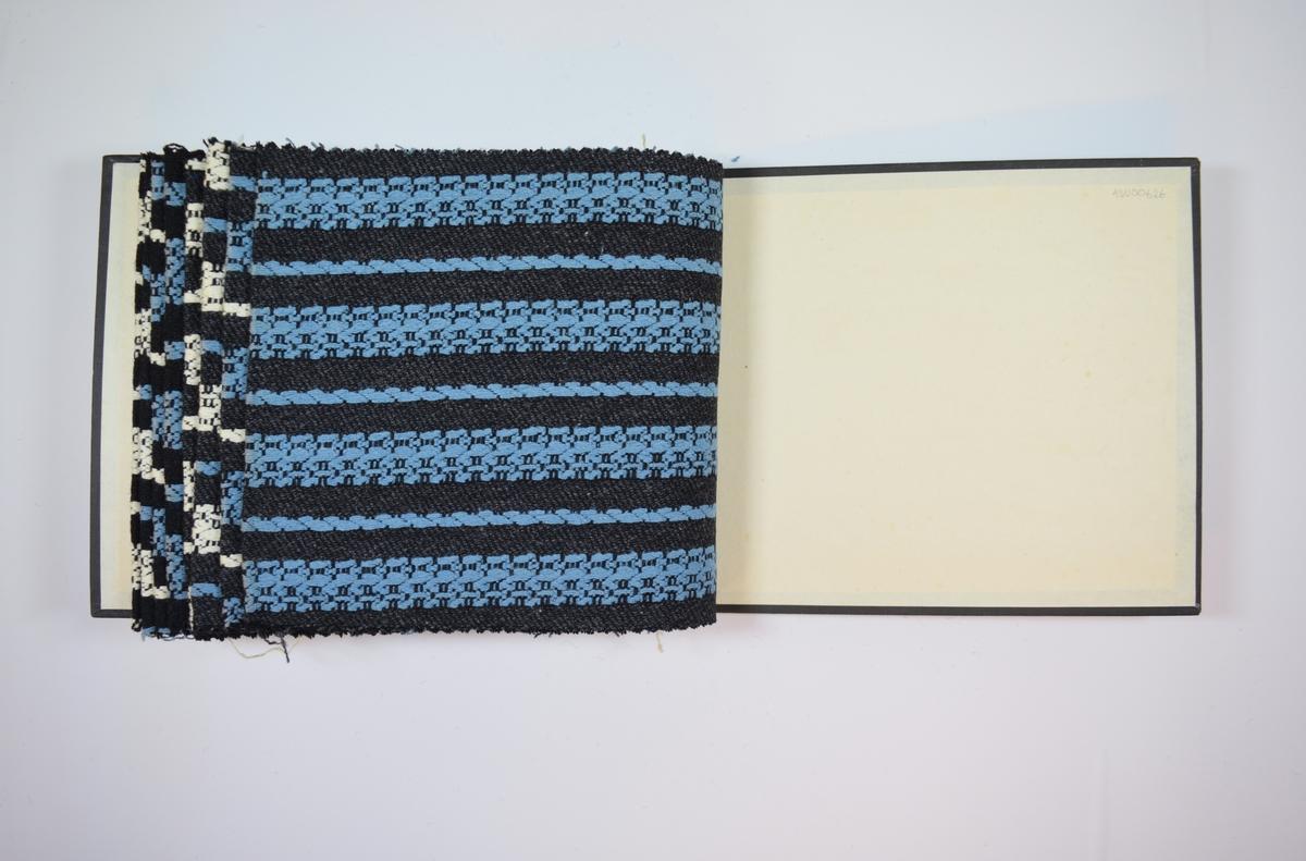Rektangulær prøvebok med åtte stoffprøver og harde permer. Permene er laget av hard kartong og er trukket med sort tynn tekstil. Boken inneholder middels tykke, tette stoff med tykke striper av to ulike mønstere. Mønsteret er det samme for alle prøvene i boken, men fargene og fargekombinasjonene varierer. De fire første stoffene har sort bunnfarge, mens de fire siste har en grå bunnfarge, ellers er variasjonen i mønsterfargene like mellom de fire første og de fire siste stoffprøvene. Stoffene er merket med en firkantet papirlapp, festet til stoffet med metallstifter, hvor nummer er påført for hånd.   Stoff nr.: 2180/8, 2180/9, 2180/10, 2180/11, 2180/12, 2180/13, 2180/14, 1280/15.