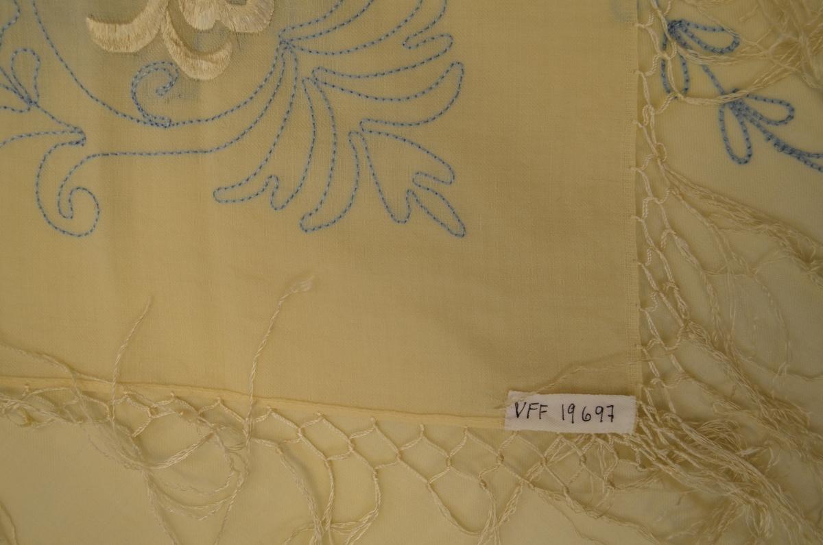 Tørkle i ubleikt ull med silkefrynser. I eine hjørna rosemønster i lyseblå tamburering.