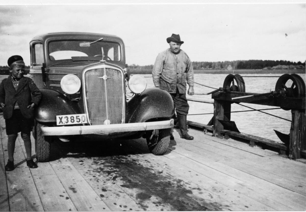 Färjan vid Norra Sundet 1935. Färjkarlen Anders Andersson (Färkar-Anders). Bilen (en Chevrolet 1934-1935) är Valfrid Lindbloms taxibil. Till vänster: Erik Lindblom (son till Valfrid).