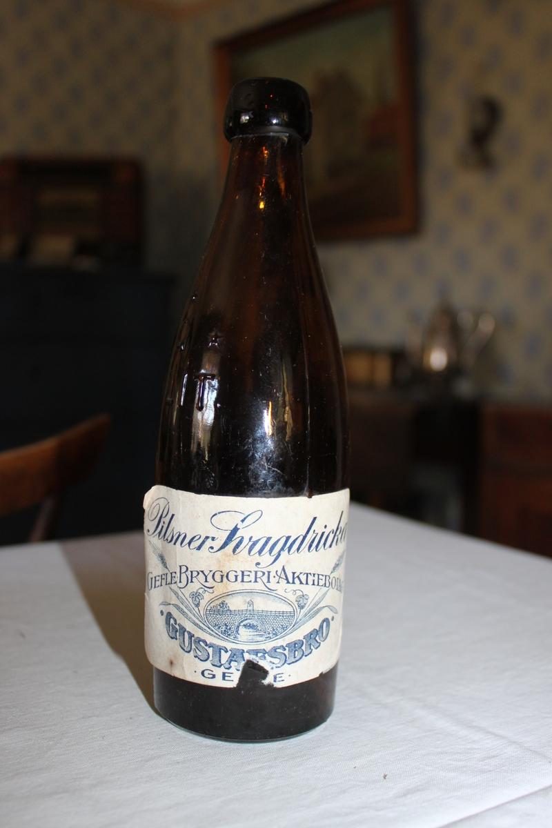 Ölflaska i brunt glas med etikett