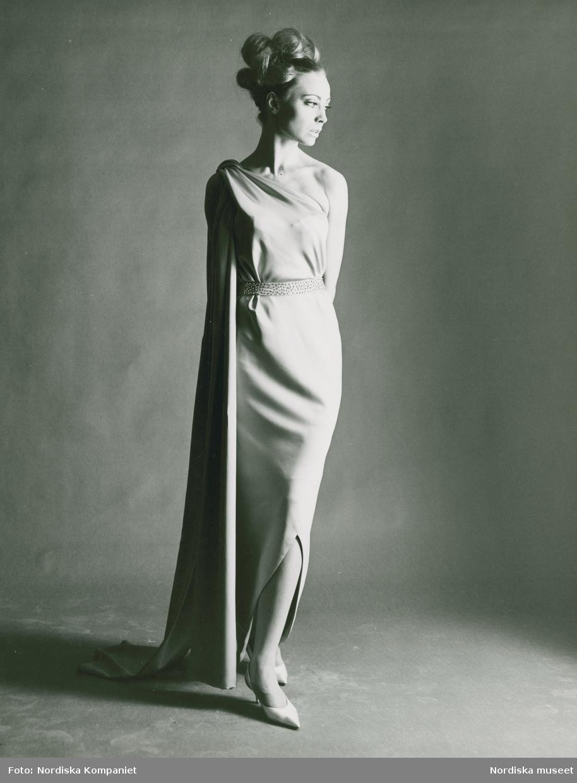 Modell i aftonklänning med slits och skärp, samt pumps. Vår, NK:s Franska, original av Balenciga.