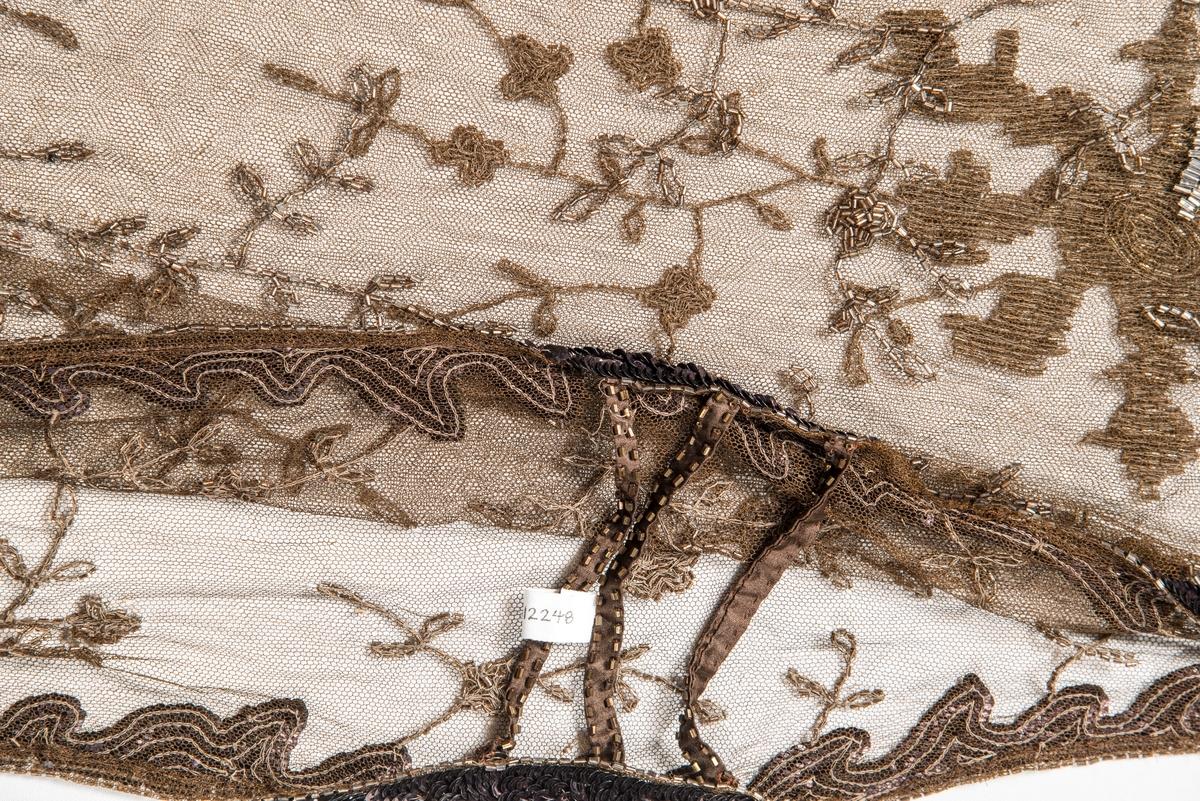 Overkjole i brun tyll med brune stråperler og palettar. Tre band i kvar side.