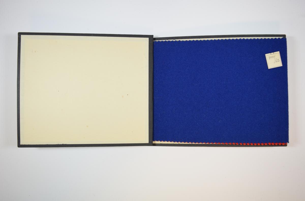 Rektangulær prøvebok med harde permer og to stoffprøver. Permene er laget av hard kartong og er trukket med sort tynn tekstil. Boken inneholder middels tykke ensfargede stoff. Kyperbinding/diagonalvev. Stoffene ligger brettet dobbelt i boken slik at vranga skjules. Stoffene er merket med en firkantet papirlapp, festet til stoffet med metallstifter, hvor nummer er påført for hånd.   Stoff nr. 7000/blå, 7000/röd.