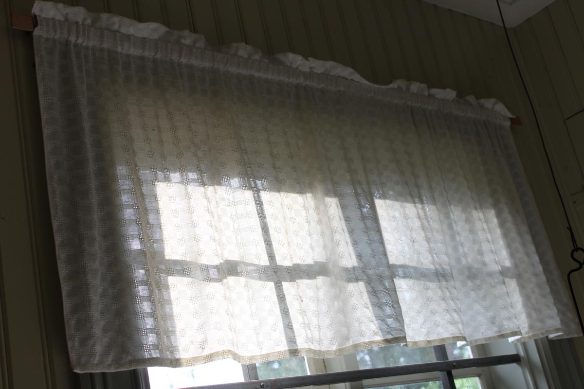 Vit gardinkappa vävd i myggtjällsteknik, vilket ger en rutig struktur i väven.