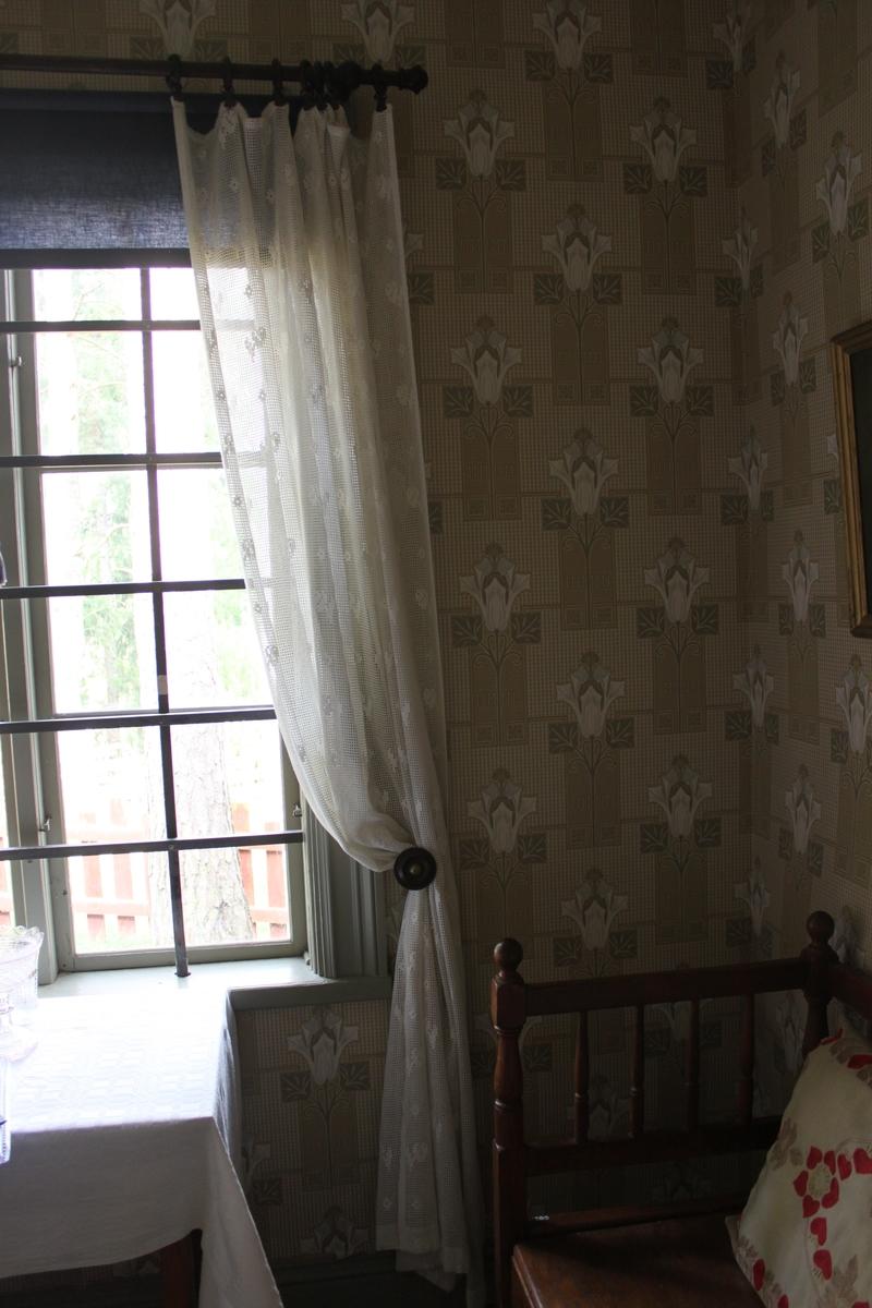 Vit, hellång gardinlängd i maskinvävd kvalitet. Rutmönster med invävt blommönster på delar av ytan. Längden ingår som en av två längder i samma fönster.