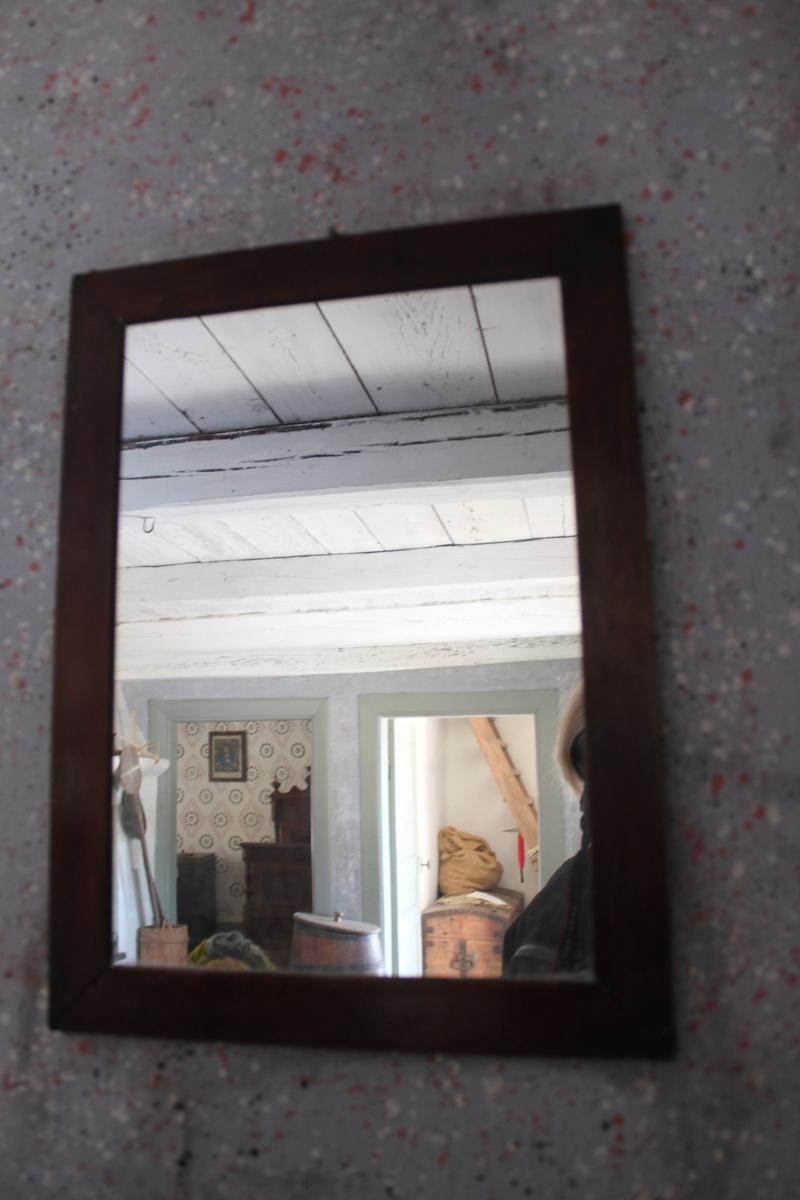 Spegel med 35 mm bred, slät ram av trä med vinkelsågade hörn. Betsad i rödbrun nyans.
