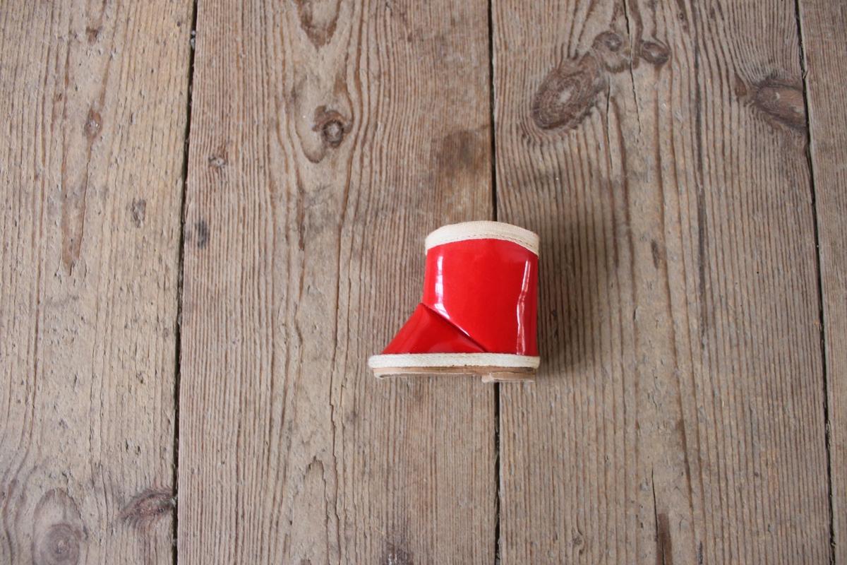 Docksko/stövel i röd plast med vita kanter i textil. Sula i brun papp, liten klack.