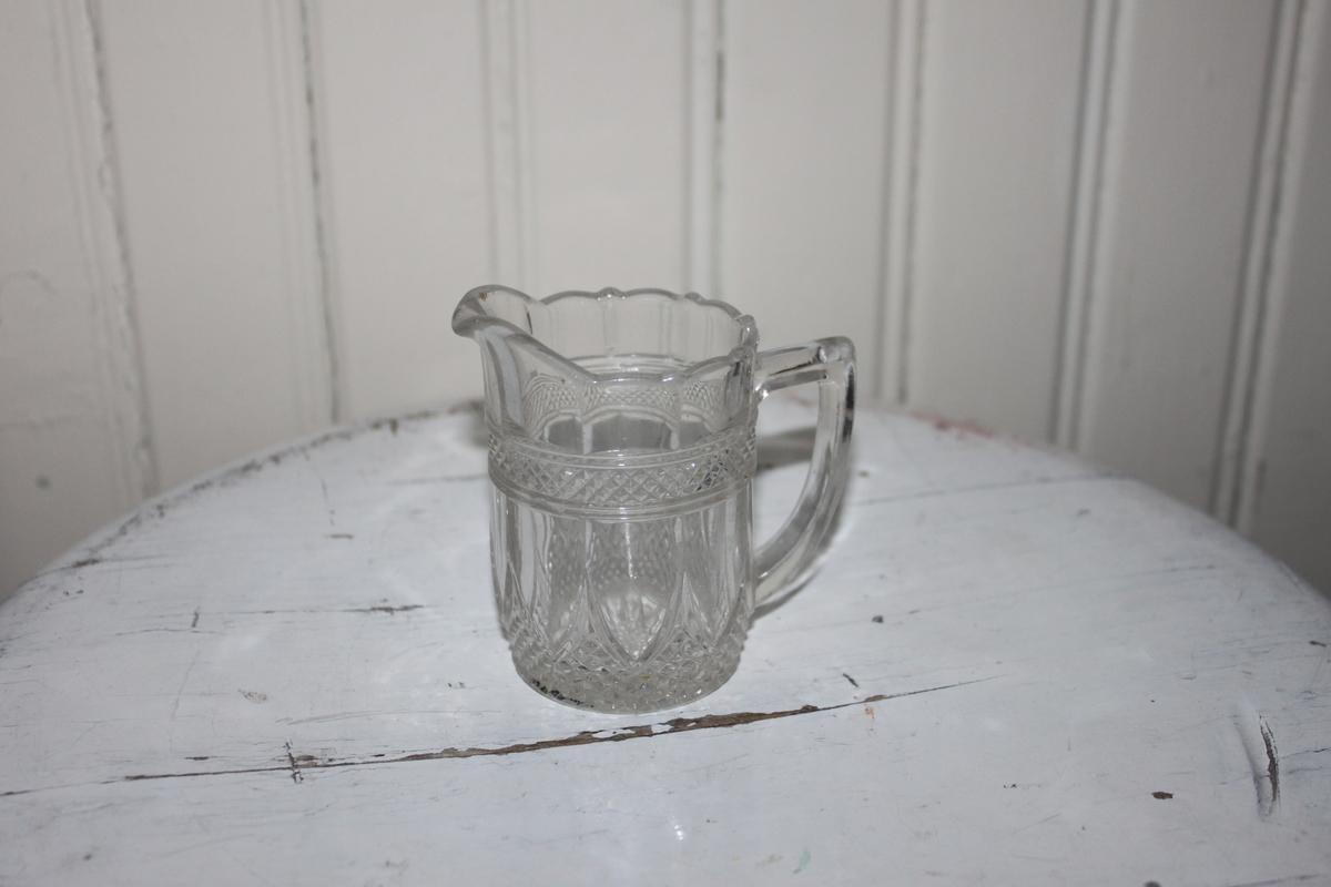 Kanna i glas för grädde. Kristallglas med dekorer. Blomma i botten