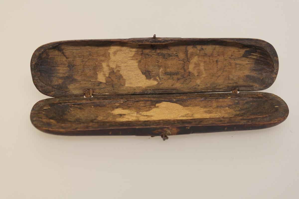 Brillehus i skåret, pusset og beiset løvtre. Hengsler og hempe er av jern. Det er skåret initialer inn på lokket.