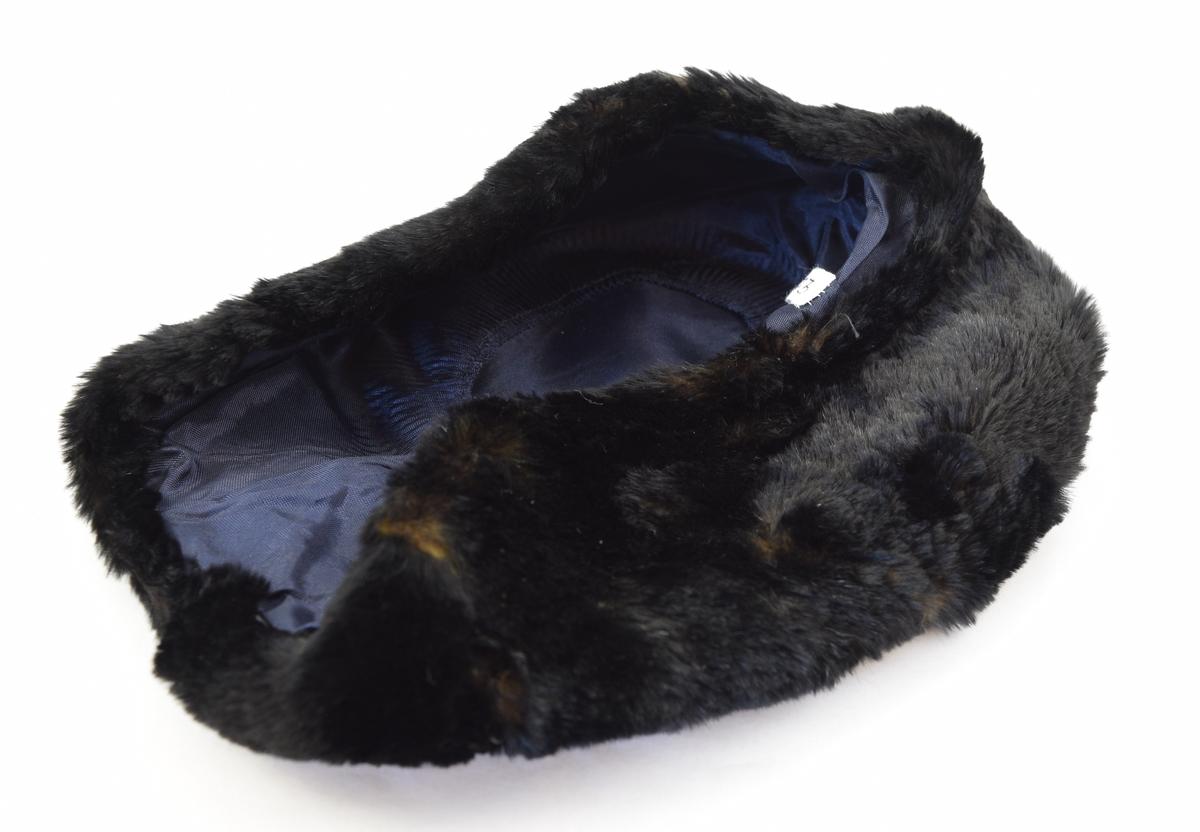 Hatt av pels med for i tynt blankt stoff. Hatten har en devis rund form og består av en rund topp med en bred kant.