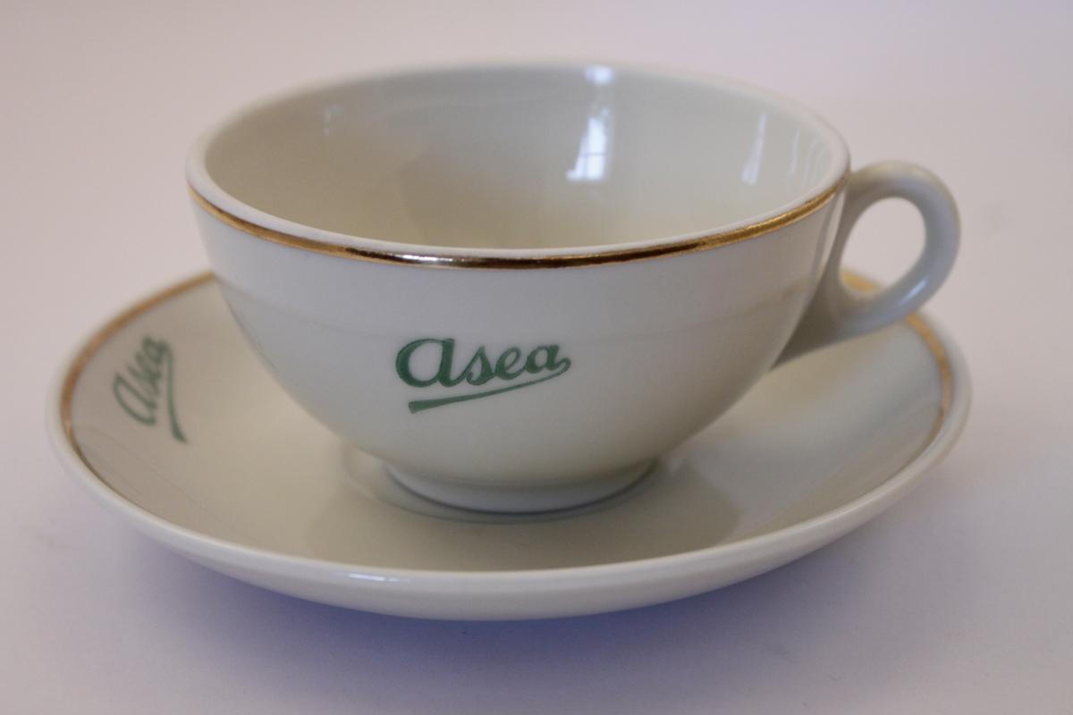 Kaffekopp med fat i cremevitt porslin med guld kanter och grön text: Asea på både kopp och fat.