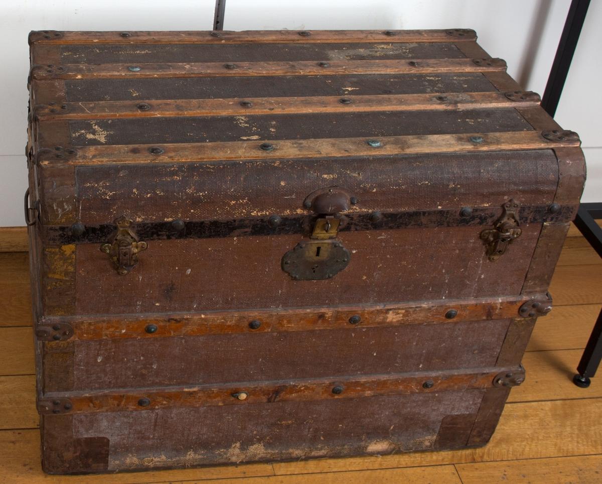 Kiste med beslag på lokk, hjørner og sider. Håndtak på begge sider. Innvendig løs romskiller i papp. Nøkkel til lås mangler.