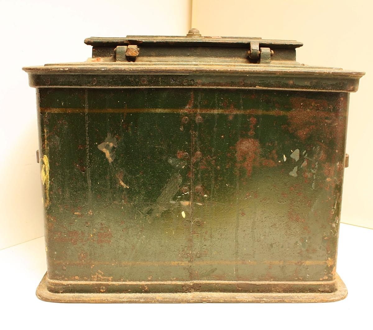 Stor, rektangulær boks med avrundede hjørner. Rester etter røde segl på toppen. Et rundt merke på forsiden.  Teknikk:  Knekt jernplate, sammennaglet på baksiden (naglesøm). Forsterket topp og bunn. Børehåndtak av flattjern.