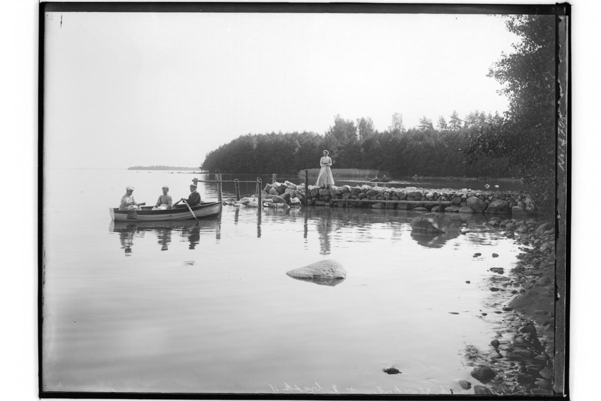 Doktor Maria FolkessonKräftfiske. En person på stenbryggan vid Hjälmaren, 3 personer i en jolle.