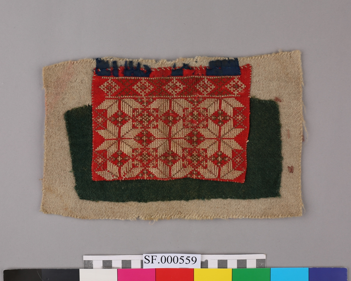 Brystduken er sydd fast til eit kvitt/grått og grønt ullstykke. Oppe langs kanten har brystduken eit blått silkeband som er delvis avslite. Åttebladroser.