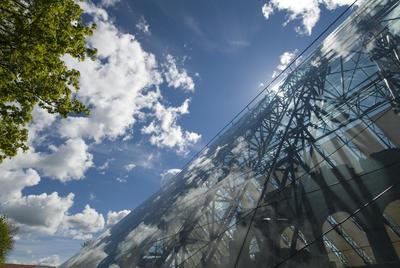 Hvite skyer speiler seg i glasset på vernebygget mens silhuetten av domkirkeruinen skimtes bak glasset.