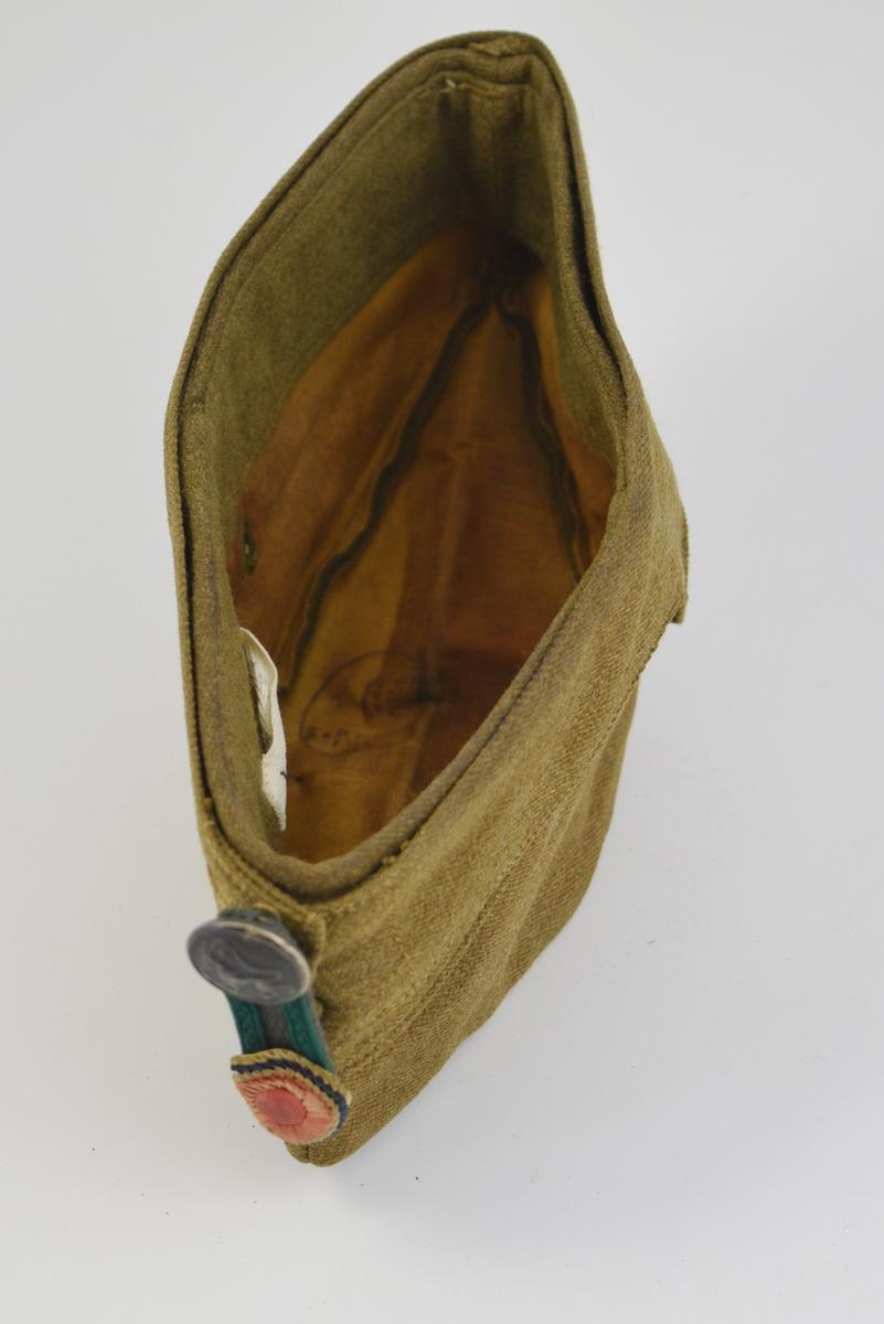 Oppbrettklaffene utgjør en del av snittet/dekoren. Smal stoffplate' tverrstilt med rosett og knapp - med den norske riksløve.