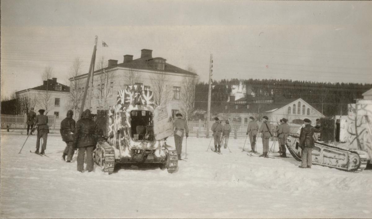Soldater på skidor och två stridsvagnar m/1921 (eller 1921-1929) på Norrbottens regementes kaserngård.