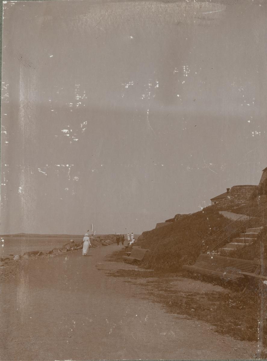 Kvinnor och män promenerar längs stranden. Till höger finns bänkar och stigen upp till Varbergs fästning.