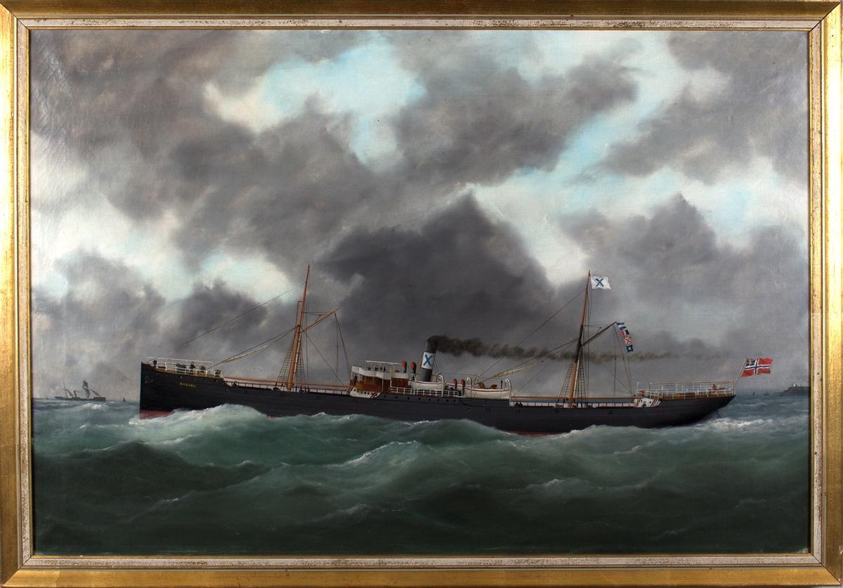 Skipsportrett av DS RAUMA under fart i åpne sjø med unionsflagg akter. Ser andre fartøyer samt land i bakgrunn, muligens utenfor Le Havre, Frankrike.