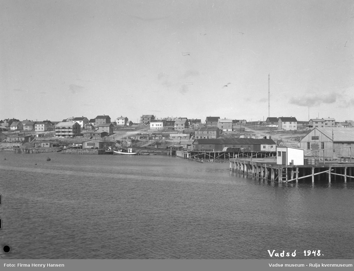 Vadsø 1948 med deler av havnen, sentrum og indrebyen. Gjenreisningen er i full gang. Vi ser kaianlegg med bygninger og fiskebåter. Vi ser også ruiner etter kaianelgg og branntomter etter bygninger. Til høyre i bildet ser vi Tollbugata som går fra sentrum og opp mot Damsveien. Til høyre sees en av radiomastene.