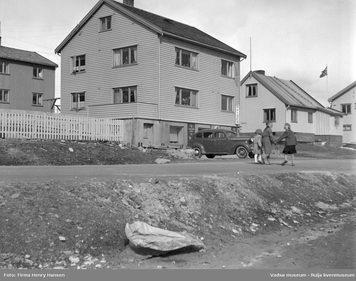 """Vadsøbilder 1952 Alrik Basmas bygg. Bildet er tatt fra syd mot nordøst. Vi ser Oscarsgata med et stort gjenreisningshus midt i bildet. Bygningen er i tre etasjer, med næringsvirksomhet i første etasje og bolig i andre og tredje etasje. I første etasje ser vi et skilt med tekst """"Aviser"""". Et skilt med """"Langaards tobak"""" skimtes også. Foran bygningen står en personbil parkert. Flere gjenreisningshus på nordsiden av gata. Tre barn i speiderdrakt spaserer på Oscarsgata. Flere vinduer står åpne, flagget vaier."""