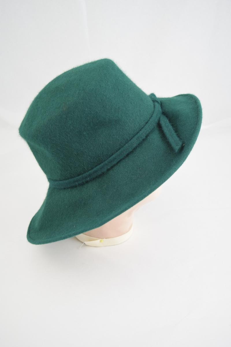 """Filt, grønn, maskinsøm. Bred brem krummet opp på en side, pull sylinderformet. I overgangen mellom pull og brem er lagt et grønt bånd av samme materiale. Båndet lagt i en løkke bak og de to endestykkene er festet løst på bremmen. På det samme bånd er festet en """"rosett"""" av svarte strutsefjær, hattens front. På innsiden av hatten er sydd et mørkere grønt hattebånd i hodeåpningen."""