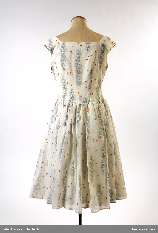 Klänning av vitt tunn nylon med crepeyta och tryckt blommönster i grått och vitt med spridda rosenknoppar i rött, gult och grönt. Avskuren i midjan, figursytt ärmlöst liv med stor urringning, 2 fram- och 1 bakstycke, i ringningen fram fastsydd rynkad uddbrodyr av bomull. Vid rynkad kjol i 4 våder, blixtlås i vänster sidsöm, livet sytt på foderstomme av vit glasig konstsidentaft, som också är underkjol kantad med smal uddbård.