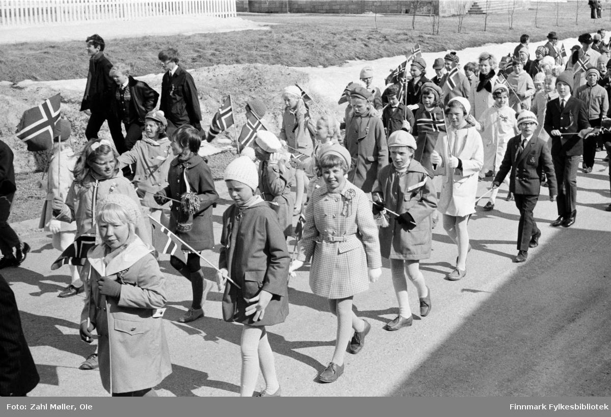 Vadsø 17.5.1969. Barnetoget passerer med flagg i hendene, pyntet i sin fineste stas og noen bærer 17.mai sløyfer på brystet. Jentene er moteriktige med hatter og kåper, strømpebukse og brune sko.  Fotoserie av Vadsø-fotografen Ole Zahl-Mölö.