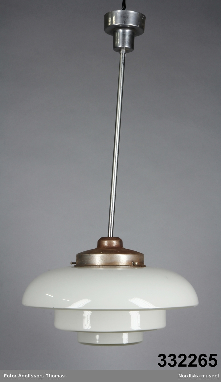 Takpendel, elektrisk, med kupa av vitt glas och upphäng av vitmetall. Halvcirkelformad sluten lampkupa, undertill indragen i två successivt mindre och platta bottnar. Kupan fixerad i upphänget med tre skruvar. Upphänget rak metallstång fäst i cylindrisk takkopp.    Spår av rost på upphänget. /Maria Maxén 2017-02-14