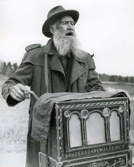 Den gamle positivhalaren, Trönö 25 september 1951. Den här mannen sjunger och spelar i Trönö 1951. Han bär en trenchcoat, hatt och har långt skägg. Han är gårdsmusikant och hans lådliknande instrument kallas för positiv. Det är ett orgelinstrument som spelar när man snurrar på veven. Av den anledningen kallades dessa musiker ofta för positivhalare.