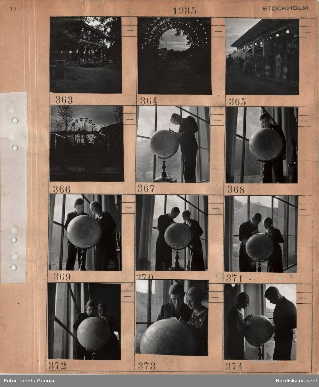 Motiv: Stockholm, Gröna Lund kvällstid, pariserhjul, ung man och kvinna som tittar på en jordglob vid ett stort fönster.