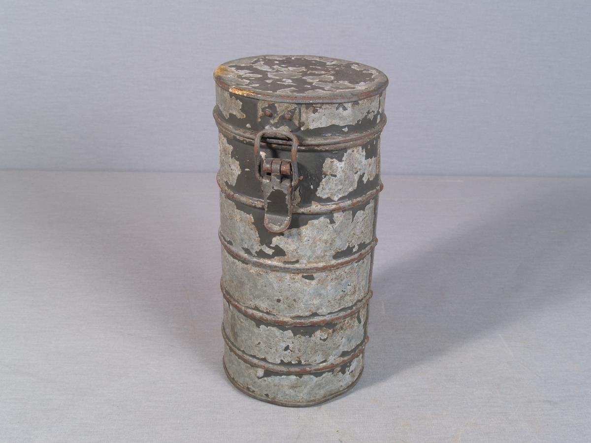 Sylinderformet beholder til gassmaske. boksen har korisontale profilringer og hengslet lokk med lås. I boksen ligger et munnstykke med tilkoblingshull for slange.