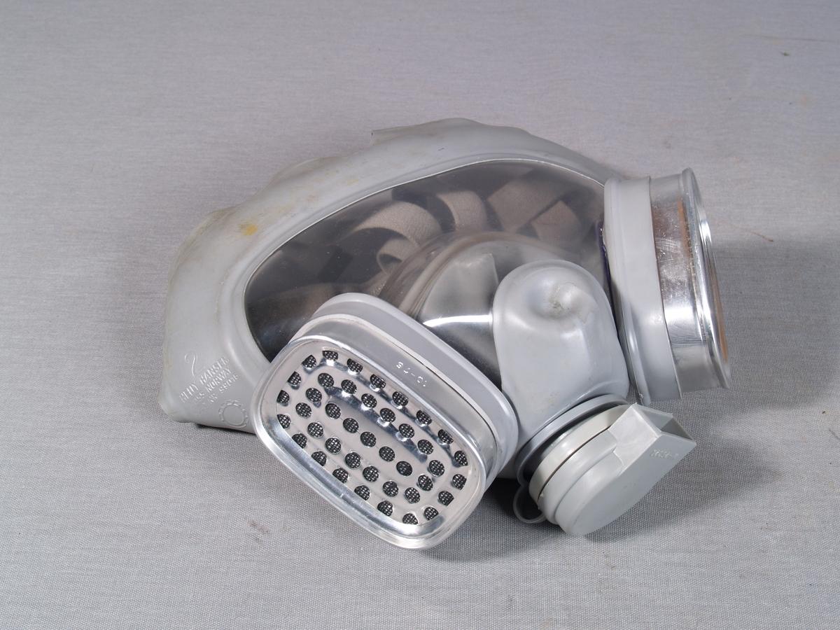Gassmaske i gummi, vindu i plast. Festestropper er i tekstil. 2 filterbokser, en på hver side påmontert. Ventil i bunnen. Munnstykke i klar plast på innsiden av masken.