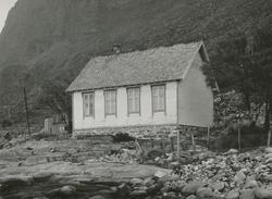 Motiv av et stuehus mellom fjæra og fjellet på Alnes. (gamme