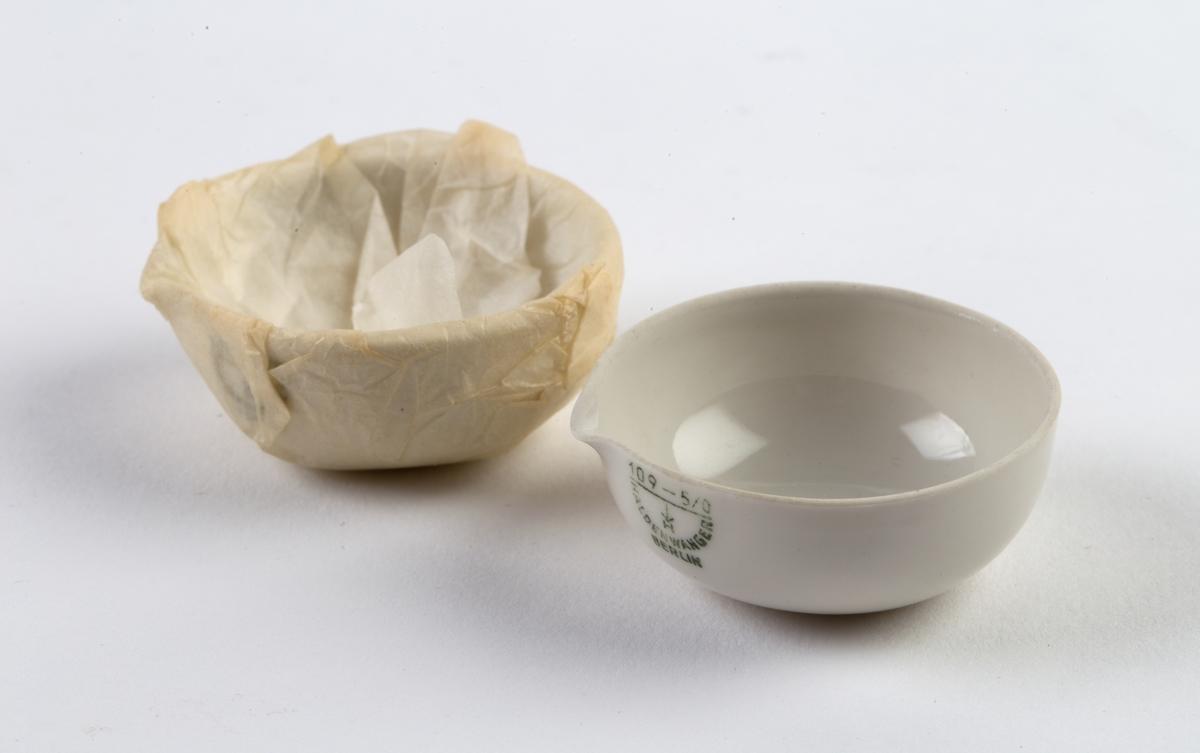 2 porselensskåler med helletut, den ene innpakket i silkepapir. Påstemplet firmalogo.