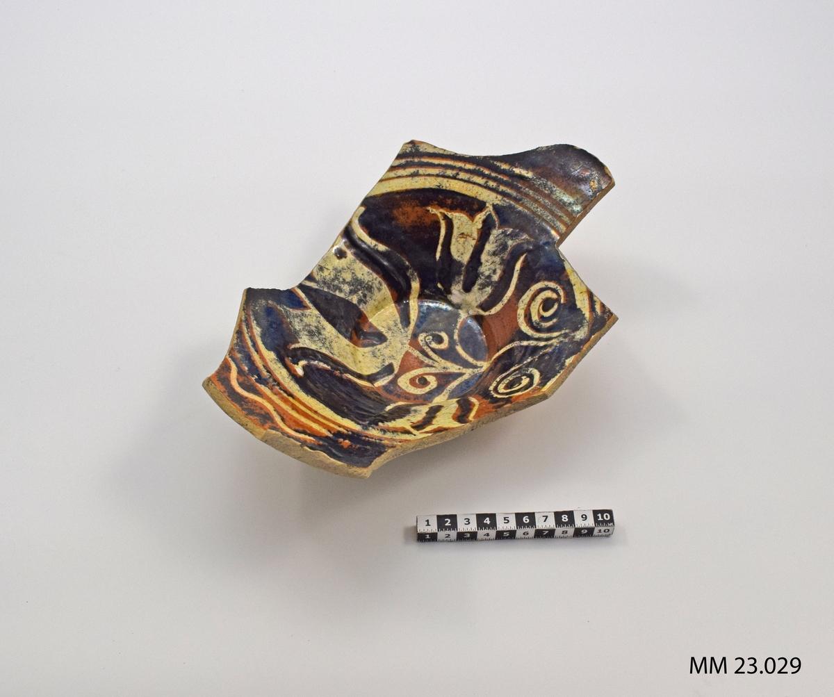 Spillkumfragmentet består av emaljerad keramik. På ovansidan finns ett mönster av emalj i färgerna vit och brun. Vissa svarta partier finns men är missfärgning. Mönstret består i huvudsak av en rund ring utmed hänkelns övre kant. Den runda ringen är i vitt och består av fyra ränder. Den yttersta ringen är vågformad. Innanför mönstret finns tre stycken tulpanklockor.