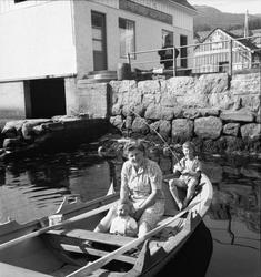 Kvinne i kjoleforkle og to barn i robåt, heimelagd fiskestan