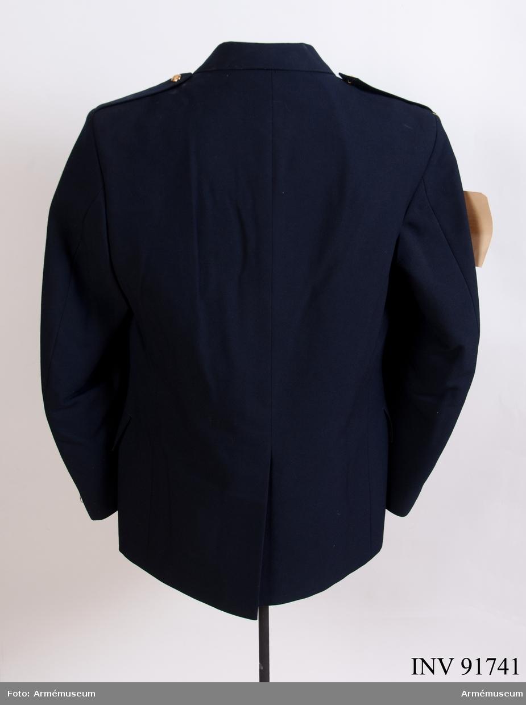 """Vapenrock sydd i blått kläde med guldfärgade knappar med Smålands vapen. Syntetfoder. Vidhängande etikett: """"1985 års uniformsutredning (UNIU-85), första förslag till daglig dräkt, M-ny för armén, utredningens tanke var att samtliga försvarsgrenar skulle ha samma färg och snitt på sitt daglig dräkt-system."""" Etikett på insidan: """"Hjelm exclusive, made in Sweden, kunglig hovleverantör""""."""