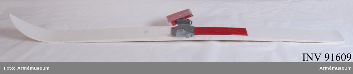 """Vit skida av kort modell. Vidhängande etikett: """"Försvarets materielverk, Originalmodell, M 5011-015001-9, Skidor korta mont, 1986-10-22, Elisabeth Rönnberg, Int T, Göran Olmarker FMV 267.4. (FMV:Bekläd) 85-09. 2000 Ex"""". Märkta på ovansidan med tre kronor, """"SF"""" och på bindningen med tre kronor. Fästningsöppning längst bak på bindningen, vilket inte finns med på de två övriga exemplaren."""