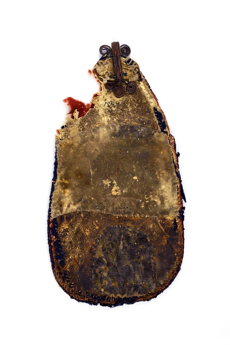 Kjolväska som är öppen upptill och har bygel av järntråd. Väskan har applikationer i blått och gult på röd botten.